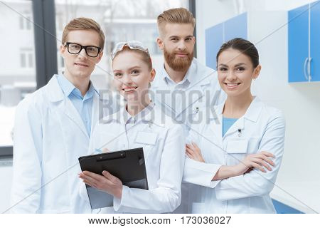 Team of young professional scientists in lab coats smiling at camera