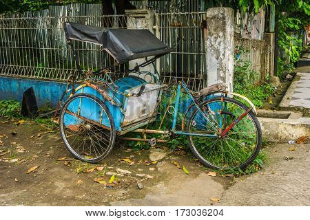 Blue pedicap or tricycle parked in side of the road near bush and wall with nobody around photo taken in Depok Indonesia java