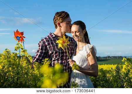Man kissing on woman forehead in mustard field on a sunny day