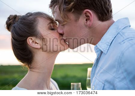 Affectionate couple kissing in field on a sunny day