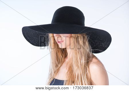 side view of woman in black hat on white