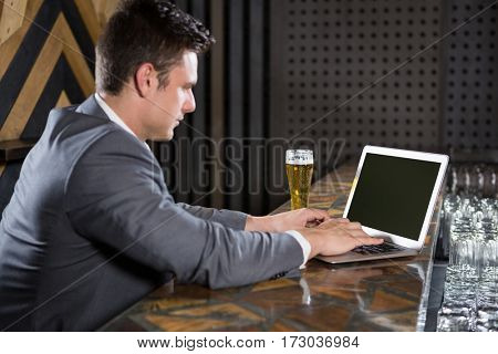 Man using laptop in bar counter at bar