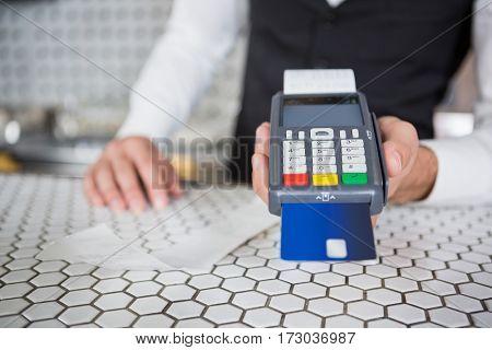 Bartender accepting a credit card at bar counter in bar