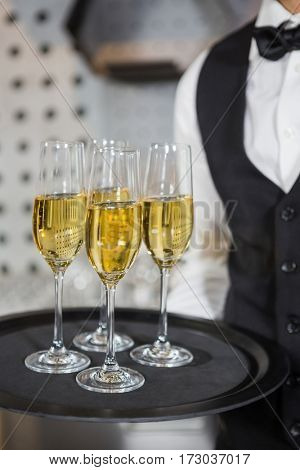 Mid section of bartender holding tray of champagne glasses in bar