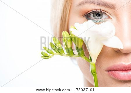 Close-up partial view of elegant blonde woman holding white flower skincare concept
