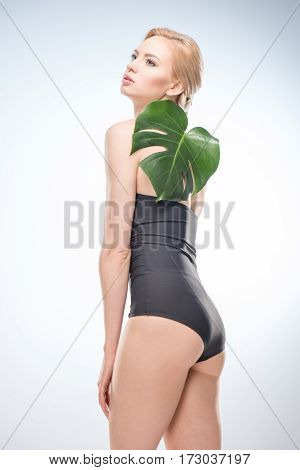 Gorgeous young woman in swimsuit holding green leaf on shoulder skincare concept