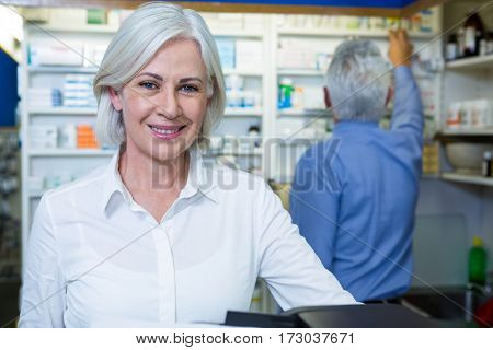 Pharmacist smiling and co-worker checking medicines in background at pharmacy
