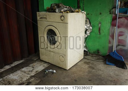 An abandoned and unused white washing machine with front door near green wall and a broom photo taken in Depok Indonesia java