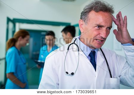 Tensed doctor standing in corridor at hospital