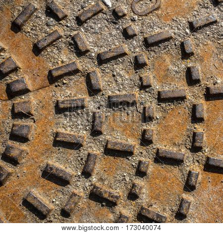 Background of metallic textures on sewer manhole