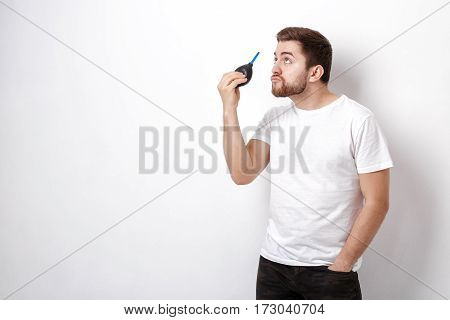 young photographer holding camera cleaning vacuum pump. rubber air blower pump dust cleaner for camera and lenses