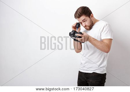 young photographer cleaning camera with vacuum pump. hand blower dust cleaner for camera and lenses.