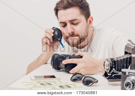 young photographer cleaning camera with vacuum pump. hand blower dust cleaner for camera and lenses. soft light
