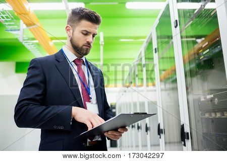 Technician looking at clipboard in server room