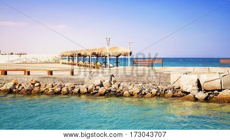 View of a pier with sunshades and the vacation spot. Egipt