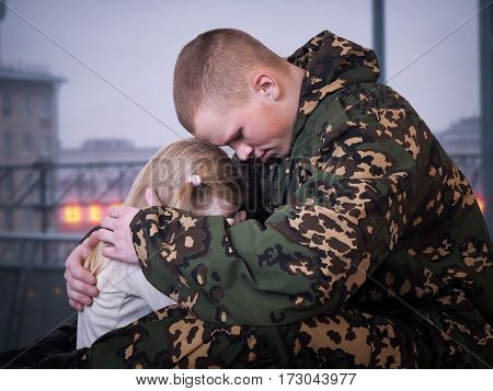 Soldier hugs baby girl. Dusk, evening. A man in camouflage uniforms