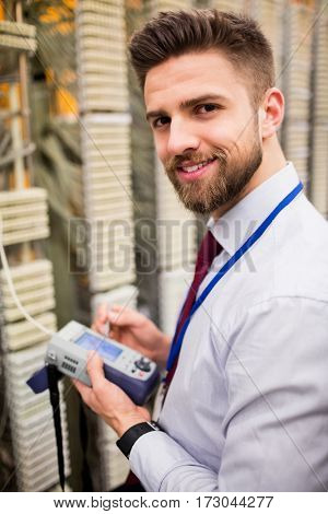 Portrait of technician using digital cable analyzer in server room