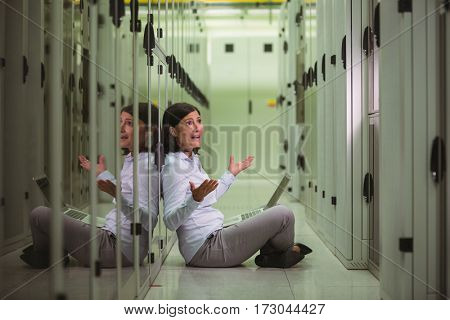 Shocked technician siting on floor with laptop in server room