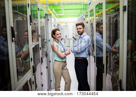 Portrait of technicians standing with arms crossed in a server room