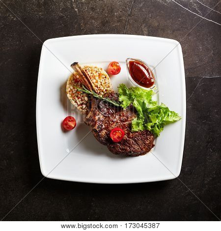 Grilled Restaurant Food - Veal Ribs Barbecue with Garnish, Sauce and Rosemary on Black Stone Background