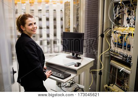 Portrait of technician working on computer while analyzing server in server room