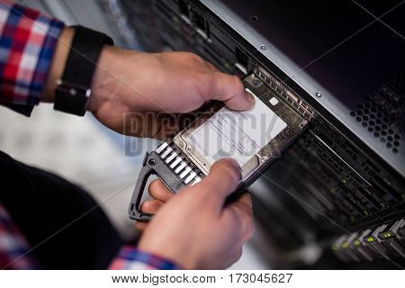 Technician inserting a hard disk drive into a blade server in server room