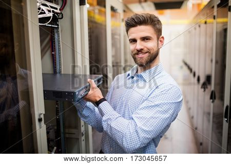 Portrait of technician removing server from rack mounted server in server room