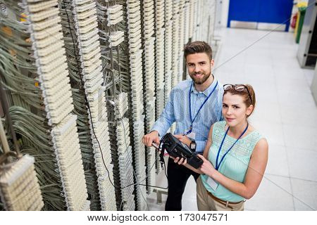 Portrait of technicians using digital cable analyzer in server room