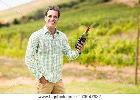 Portrait of smiling vintner holding bottle of wine in vineyard