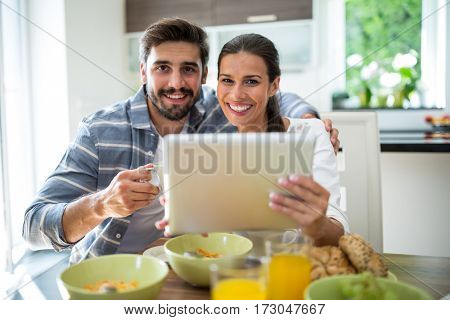 Portrait of couple using digital tablet while having breakfast at home