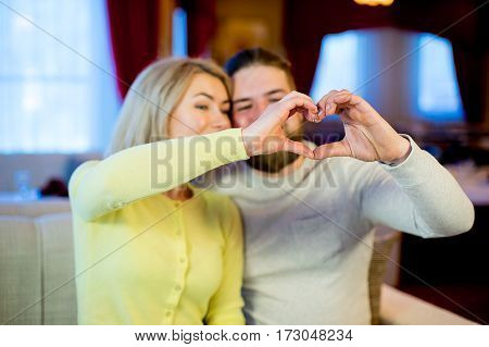 Happy couple showing a heart shape with their fingers