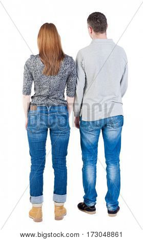 Back view of young embracing couple (man and woman) hug and look into the distance. beautiful friendly girl and guy together. Rear view people collection.