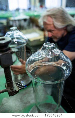 Glassblower working on a glass at glassblowing factory