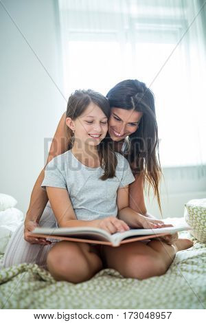 Mother and daughter reading book on bed at home