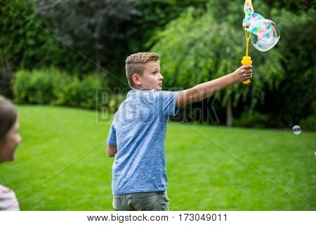 Kids playing with bubbles in the park on a sunny day