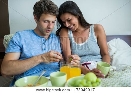 Smiling couple having breakfast on bed at home