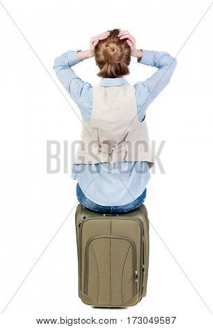 back view of shocked woman  in vest sits on a suitcase. beautiful  girl in motion.  backside view of person.  Rear view people collection. Isolated over white background.