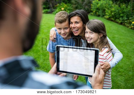 Father clicking picture of family from digital tablet in park on a sunny day