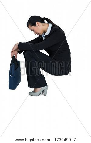 Depressed businesswoman sitting with handbag against white background