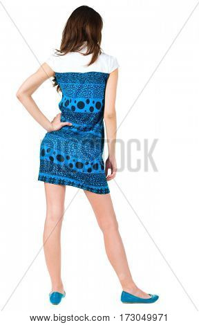 back view of standing beautiful brunette woman. Young girl in blue dress looking ahead of yoursel. Rear view people collection.  backside view of person. Isolated over white background.