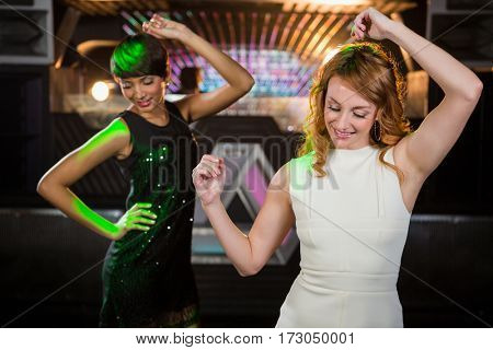 Smiling female friends dancing on dance floor in bar
