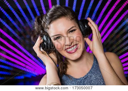Pretty female DJ playing music and singing at nightclub