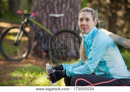 Portrait of female mountain biker holding water bottle in the forest