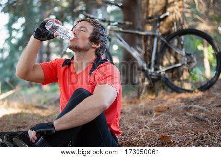 Male mountain biker drinking water in the forest