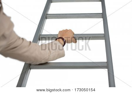 Businesswoman holding ladder against white background