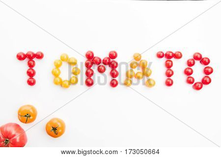 colorful tomato word made with cherry-tomatoes on white