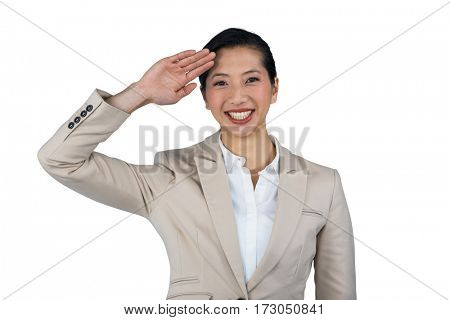 Portrait of businesswoman saluting against white background