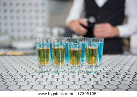 Glass of blue lagoon drinks and whisky on bar counter and bartender standing in background