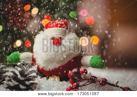 Santa claus and pine cone on snow during christmas time