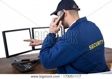 Rear view of security officer talking on phone while pointing at computer monitors